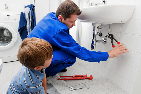 plumber fixing sink with boy watching